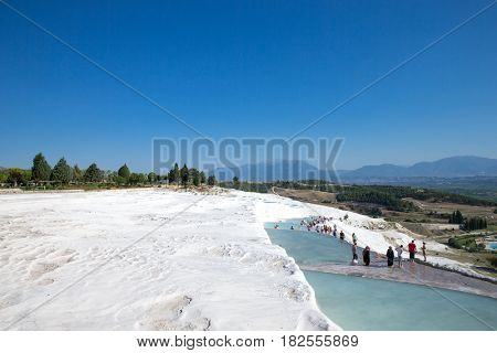 Pamukkale, Turkey - August, 14 2015: Tourists on Pamukkale Travertine pools and terraces. Pamukkale is famous UNESCO world heritage site in Turkey