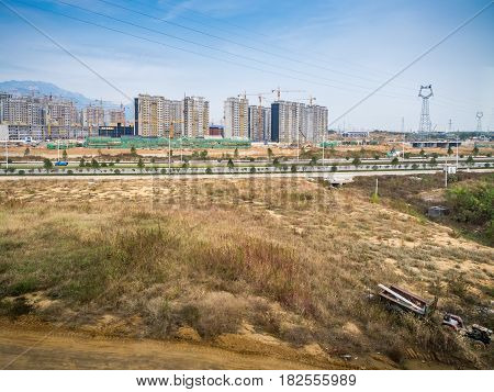 Tianjin, China - Nov 1, 2016: New small town with high rise buildings under construction outside Tianjin City. Captured from within a High-Speed Rail (HSR), showing a supply of electricity power lines.