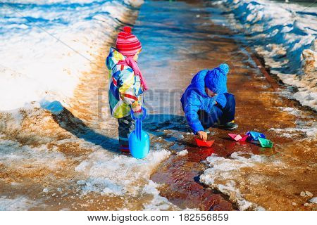 little boy and girl plaing with paper boats in spring nature