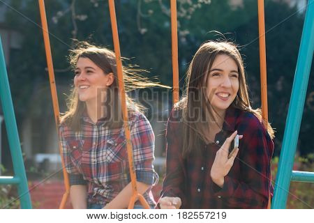 Portrait of two happy smiling teenage girl on the swing