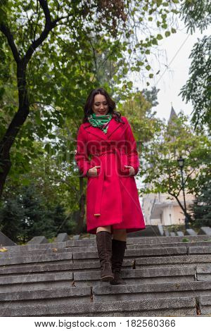 Beautiful woman in a red coat walking down the stairs. People