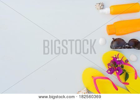 Summer beach fun - border of sandals with glasses and sunscreens