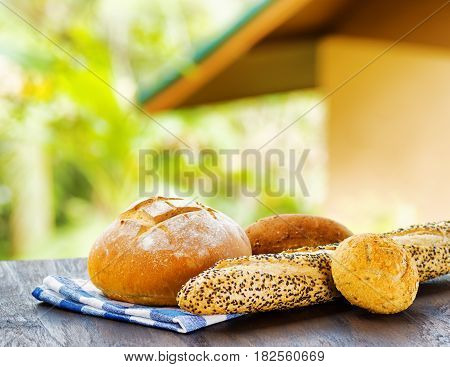 Fresh Bread And Checkered Napkin On Wooden Table On Rural Background