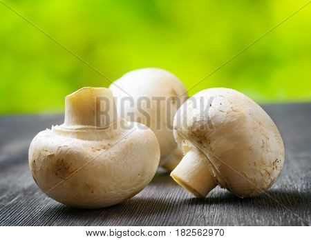 Fresh Champignons On Black Wooden Board.