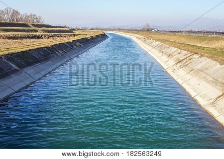 Irrigation canal between agricultural crops in italy