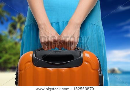 Woman In Blue Dress Holds Orange Suitcase In Hands On Tropical Landscape Background