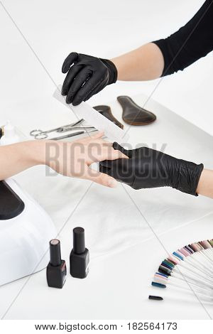 Professional nail artist working with nail file making square nails while doing manicure at salon.