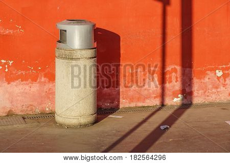 trash can trashcan dustbin garbage rubbish bins waste round outside in street against brick wall with brick copy space residential