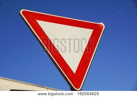 roadsign, give priority with blue sky in background .