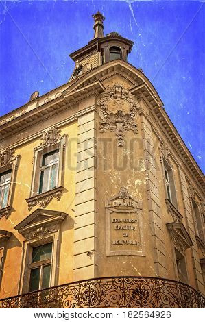 Old photo with stone facade on classical building with ornaments and sculptures. Belgrade Serbia. Vintage processed.