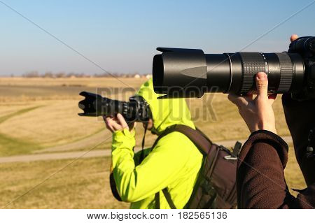Two wildlife photographers with long lens in the nature