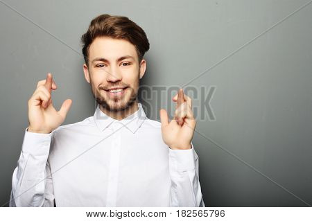 Portrait of young business man in shirt keeping fingers crossed while standing against grey background
