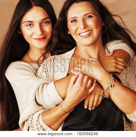 cute pretty teen daughter with mature mother hugging, fashion style brunette makeup close up, real happy family
