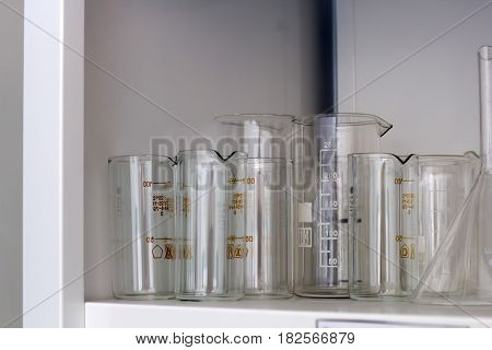 glassware for chemical analysis on the shelves in the lab