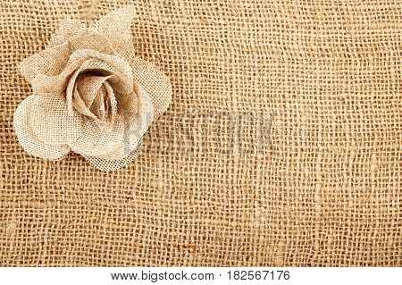 rose made of sackcloth material on sackcloth texture with copy space