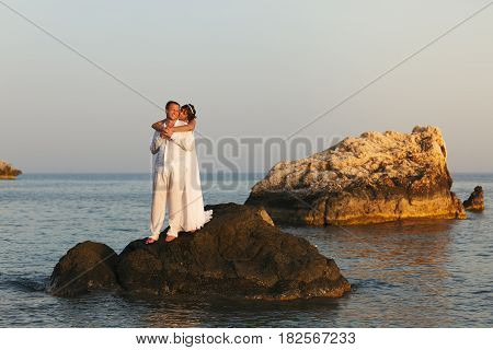 Bride Leans To A Groom Hugging Him From Behind While They Stand On The Stone In A Sea