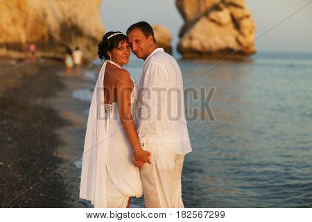Bride And Groom Look Over Shoulders Standing On The Sea Shore