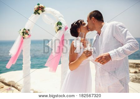 Bride And Groom Kiss Standing Behind A Wedding Altar With Champagne Flutes