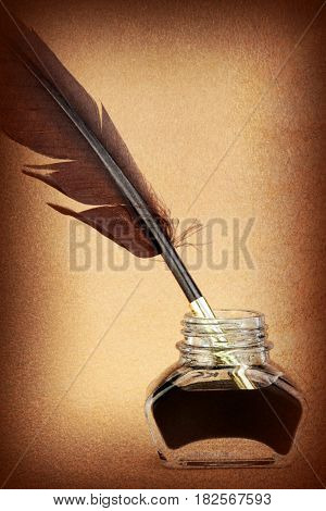 Quill pen in ink bottle on brown background