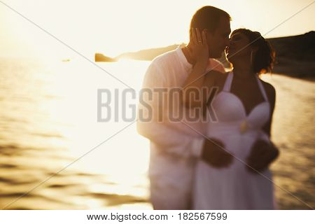 Sunset Shines Behind A Happy Newlyweds Standing In The Sea Water