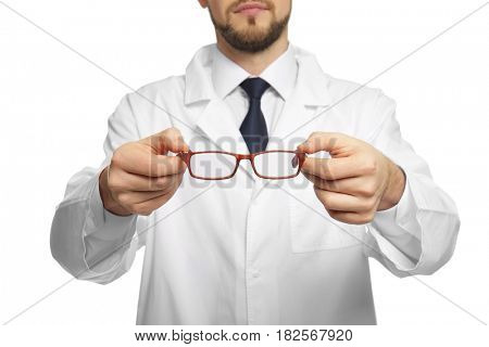 Handsome ophthalmologist holding glasses on white background