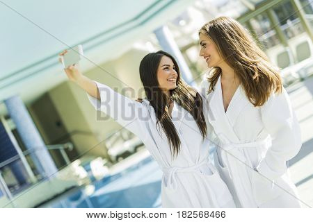 Two beautiful girls taking a selfie next to a swimming pool