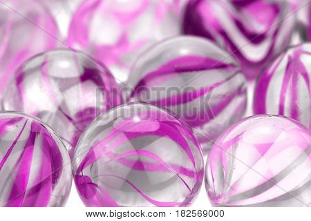 Pink glass marbles on white background .