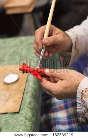 The artist draws a doll-matryoshka. Hand closeup.Photo.