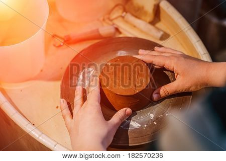 Potter makes clay pot on potter wheel in workshop, handmade craft, hands close up, view from above