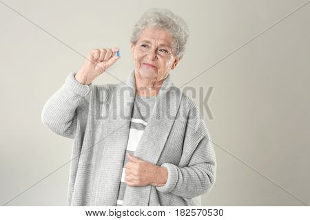Elderly woman with pill on light background