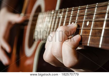 Guitarist withguitar. The hands on the strings of a guitar fretboard. Accord on a musical instrument. Shallow depth of field.