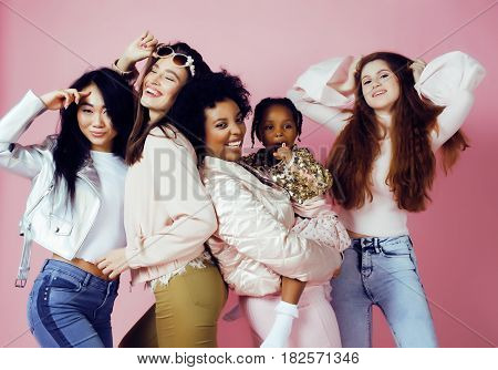 three different nation girls with diversuty in skin, hair. Asian, scandinavian, african american cheerful emotional posing on pink background, woman day celebration, lifestyle people concept close up