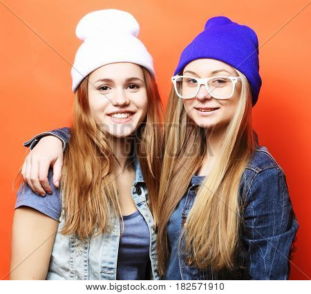 lifestyle and people concept: Two young girl friends standing together and having fun. Looking at camera.Yellow background.