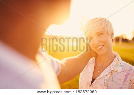 Point of view portrait of a romantic african american hipster touching the face of his girlfriend in love in city parc holding hands at sunset with flare sunlight. Artistic golden sunflare serie