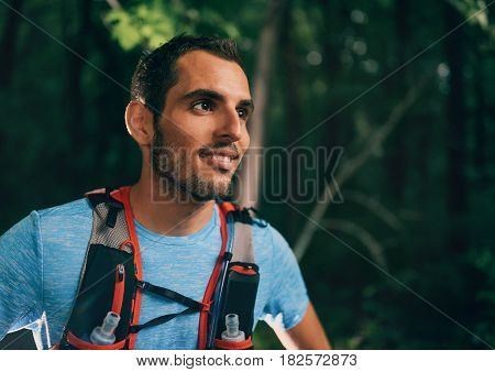 Portait of a competitive, athletic millennial man taking a break before running off road outdoors through the woods on a trail in the afternoon wearing sportswear.