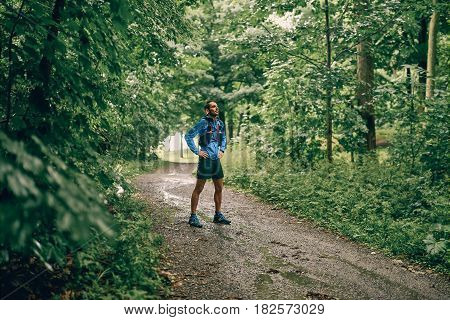 Competitive, athletic young man runs off road outdoors through the woods woods in mud and water puddles on a trail in the afternoon wearing sportswear.