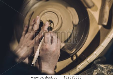 Potter shapes the clay product with pottery tools on the potter's wheel, top view, toned, selective focus on hands