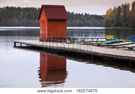 Small Red Barn On Floating Pier With Moored Boats