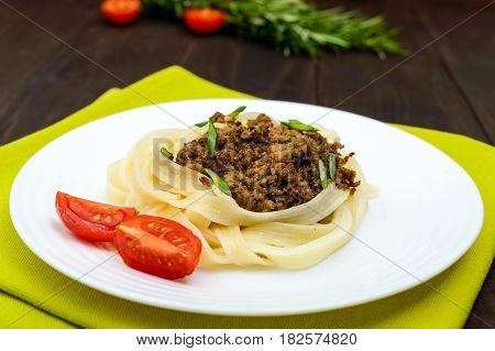 Pasta nest tagliatelle with bolognese sauce on a plate on a dark wooden background