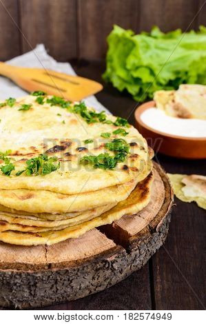 Thin flatbread - traditional Asian bread on a dark wooden background. Vertical view