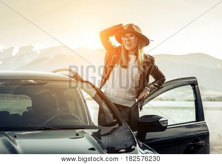 Woman at spreeng time. Yoyng happines female in hat and sunglasses stay near her black car at sunny day.