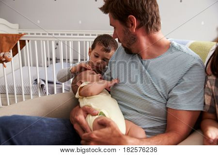 Father With Son And Newborn Brother In Nursery