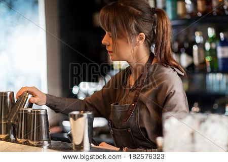 alcohol drinks, people and luxury concept - barmaid with shakers preparing cocktail at bar