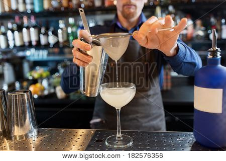 alcohol drinks, people and luxury concept - barman with shaker and strainer preparing cocktail and pouring it into glass at bar