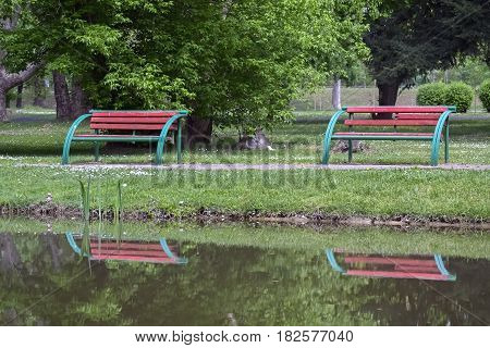 Two empty benches in the city park reflecting in the water