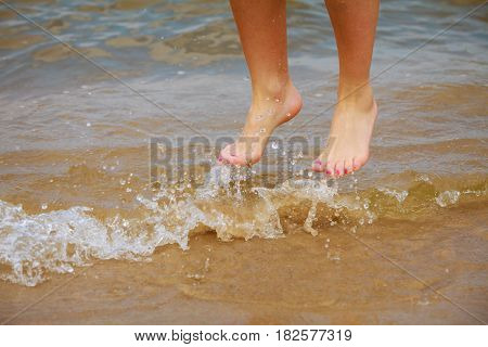 Female Feet Jump On Beach.