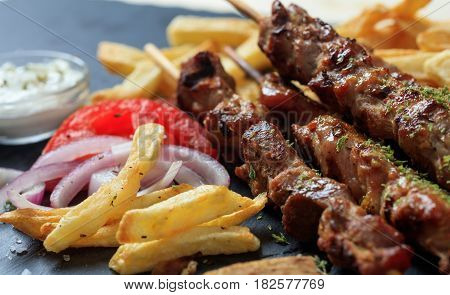 A Grilled meat skewers and fried potatoes