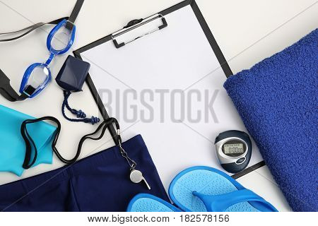 Swimming set and clipboard on light background