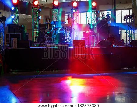 empty stage in a room with red lights, smoke and music equipment