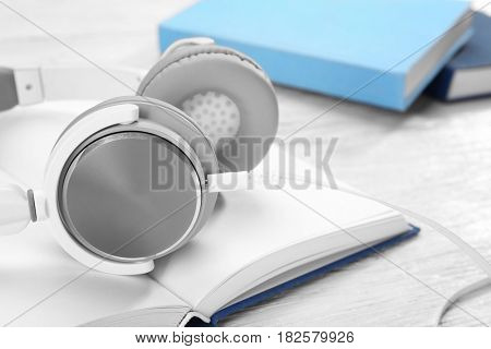 Audiobook concept. Open book with headphones on wooden background, closeup